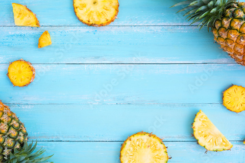 Fotografia Tropical pineapple on wood plank blue color