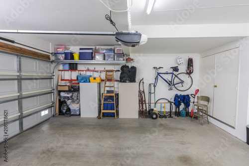 Photo  Organized clean suburban residential two car garage with tools, file cabinets and sports equipment