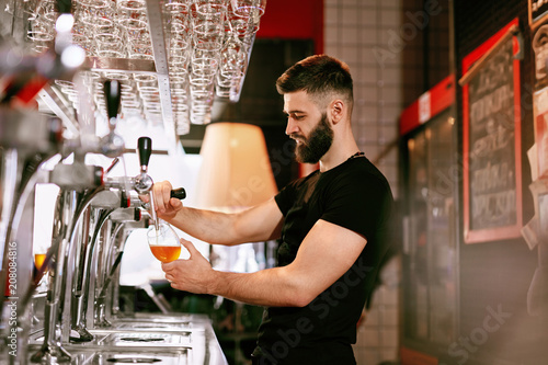 Fotografía  Bartender Working At Bar Pub Pouring Beer In Glass