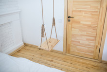 Wooden Swing  With Rustic Ropes In The Room Loft Interior. White Apartment With Bricks Walls.