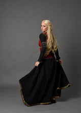 Full Length Portrait Of Pretty Blonde Lady Wearing  A Red And Black Fantasy Medieval Gown. Standing Pose On Grey Background.