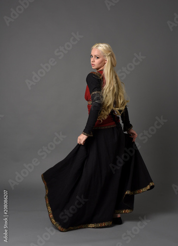 Photo full length portrait of pretty blonde lady wearing  a red and black fantasy medieval gown