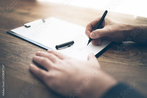 Fotomural  close-up shot of businessman signing contract or document on wooden desk