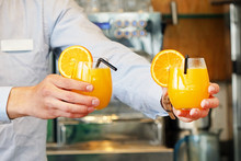 The Barman Gives Two Glasses Of Orange Juice To The Client Of The Hotel Restaurant. The Waiter Transfers The Order For Two Orange Juice To The Client Of The Hotel Bar. The Concept Of Service.