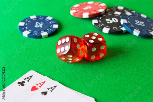 фотография  Dice, poker chips and playing cards on the green table