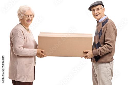 Elderly man and an elderly woman holding a big cardboard box