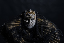 Ancient King Of Fairy Tale World Sitting On Throne, Fantasy Concept. Old Bearded Blind Man Thorns On His Head Isolated On Black Background. Creepy Magician In Metallic Golden Gown In Dark Room
