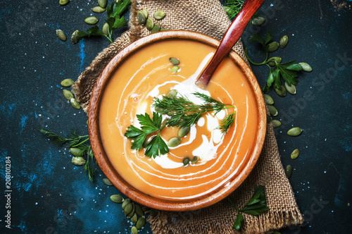 Valokuva Creamy pumpkin soup with herbs and seeds in wooden bowl, rustic style, black bac