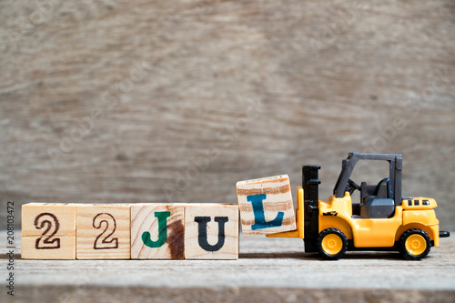 Poster  Toy forklift hold block l to complete word 22 jul on wood background (Concept fo