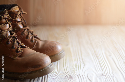 Fotografía  Yellow leather used work boots on wooden background closeup