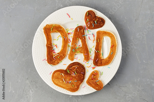 Special Father's Day breakfast. Alphabet Pancakes with sprinkles on white round plate. Top view, close up
