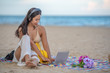 Smiling attractive Asian woman with happiness and enjoying on the beach, use headphone listening music from laptop computer, summer relaxing time concept.