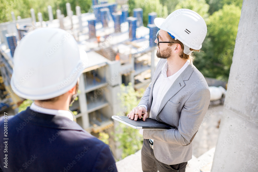 Fototapeta Two engineers or architects supervising the process of residential building construction standing on the structure outdoors