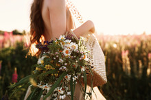 Woman Holding Wildflowers Bouquet In Straw Bag, Walking In Flower Field On Sunset. Horizontal Noface Still Life