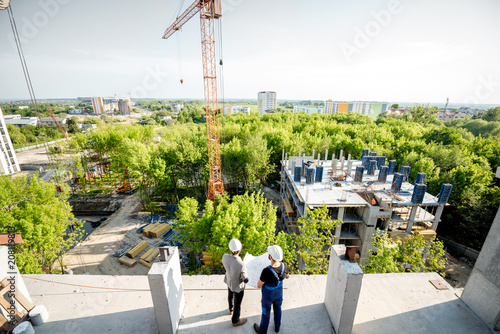 Top view on the construction site of residential buildings on the green area with two workers looking on the construction process