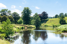 View Of A River In Summertime As Sheep Graze In The Middle Ground. Photo Of The Derwent River At Chatsworth Park In The Peak District, Derbyshire, England