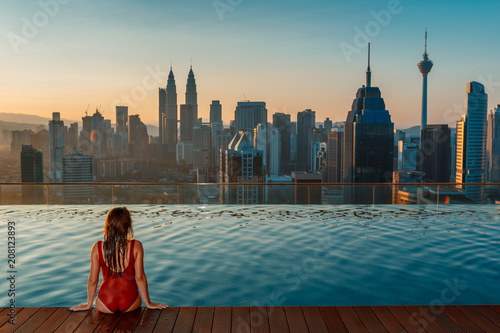 Canvas Prints Kuala Lumpur Asian travel and vacation. Young woman enjoying the city view from roof top swimming pool.