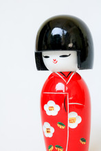 Japanese Wooden Doll Wearing A Red Kimono