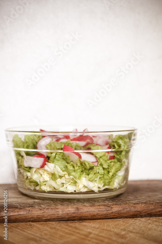 Tuinposter Klaar gerecht Vegetable vegan salad of wild garlic, radish, spring onions, cabbage and lettuce in a large transparent dish on an antique wooden background. Close-up, top view, flatlay. White background.