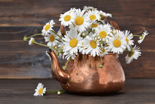 Daisy Flowers In A Vintage Teapot On Wooden Background