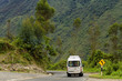 Van takes the curve of a road with signal between mountains of Ollantaytambo, Peru