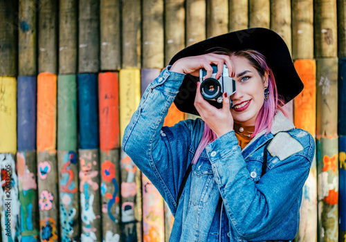 Image of a young female photographer standing in front of colorful wall.