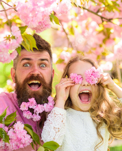 Father and daughter on happy face play with flowers as glasses, sakura background. Girl with dad near sakura flowers on spring day. Child and man with tender pink flowers in beard. Family time concept