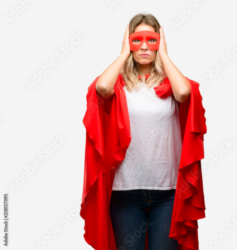 Young super hero woman wearing cape covering ears ignoring
