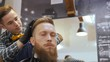 Hairdresser for men. Barbershop. Caring for the beard. Barber with hair clipper works on hairstyle for bearded guy barbershop background. Hipster lifestyle concept. Barber with clipper trimming hair