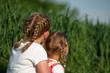 Dwie dziewczynki, blondynki uczesane w warkoczyki, nastolatka i kilkulatka, siedzą razem, blisko siebie, na zewnątrz, tyłem, w tle  bujna wiosenna (letnia) zieleń