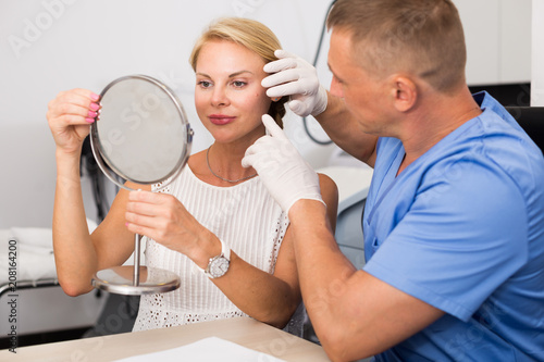 Deurstickers Akt Specialist is analysing skin of female patient with using mirror before the procedure