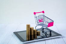 Step Of Coin Stack And Shopping Cart Or Supermarket Trolley On Tablet Computer Screen On White Working Table, Business And Finance Concept.