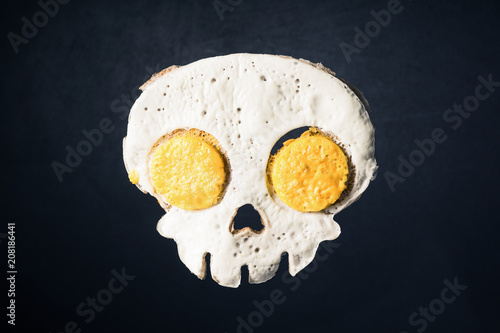 Fried eggs in the skull shape against darken background
