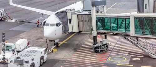 Photo avion gros-porteur relié à sa passerelle d'embarquement