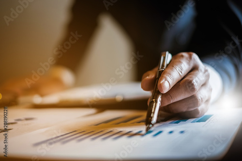 Leinwand Poster An Accountant man holding pen and using calculator do tax of company on wooden desk in office