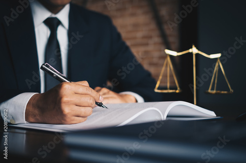 Obraz Close up lawyer businessman working or reading lawbook in office workplace for consultant lawyer concept. - fototapety do salonu
