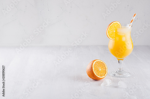 Staande foto Cocktail Colorful orange cool citrus cocktail with slice oranges, ice cube, straw on white modern wooden background.