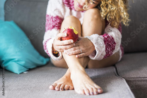 Fotografia  sweet and tender lonely caucasian lady at home sitting on the sofa eating a healthy red apple