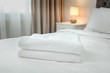 Stack of towels on bed in modern hotel room
