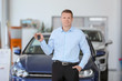 Handsome young salesman holding key in car dealership
