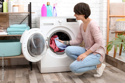 Printed kitchen splashbacks Artist KB Young woman putting clothes into washing machine at home