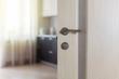 Wooden door with metallic handle open in to the empty kitchen