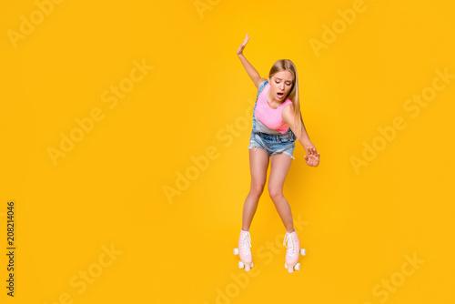 Fotografia Portrait of nervous depressed girl learning roller skating carefully keeping bal