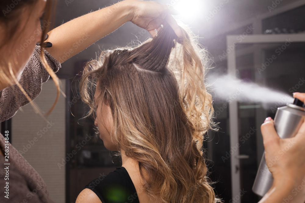 Fototapeta Back view of professional hairdresser fixing a coiffure with curls of a young client using a hair spray in a beauty salon
