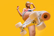 canvas print picture - Bottom view of roller skate step on camera, cheerful joyful playful funky girl showing equipment for fitness workout isolated on yellow background