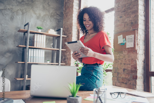 Portrait of cheerful stylish journalist in casual outfit sitting on desk holding gadget in hands using wi-fi internet in modern office with interior. Electronic wireless device concept