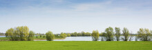 Beautiful View On A Typical Dutch Landscape Near The River Waal And Zaltbommel, Water, Green Grass, Meadows, Floodplains  And Trees On A Sunny Day In April, Springtime