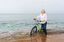 Blond Woman Wading Through The Sea With A Bike