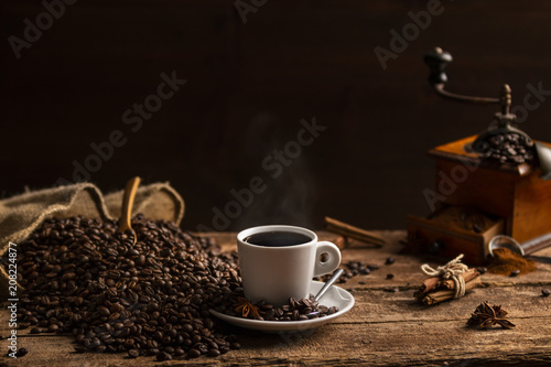 Cup of coffee with coffee beans and grinder on wooden table