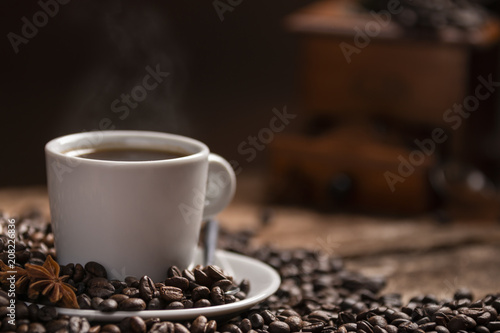 Spoed Foto op Canvas Cafe Cup of hot coffee with coffee beans on wooden table